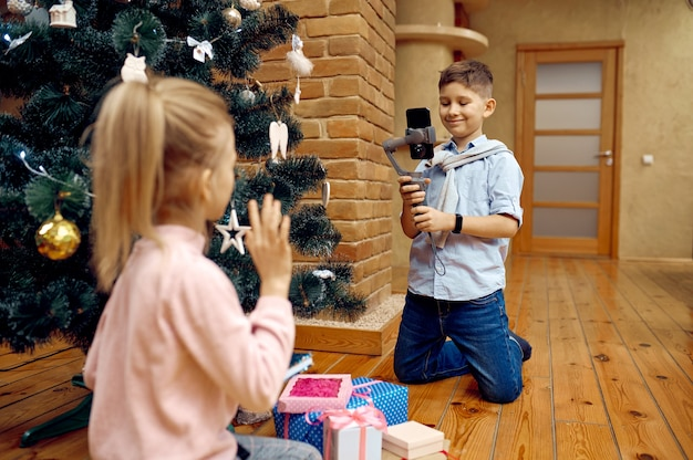 Детские блогеры записывают рождественский видеоблог на телефон. детский блог в домашней студии, социальные сети для юной аудитории, онлайн-трансляция