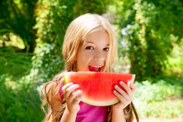 Children blond little girl eating watermelon slice in forest