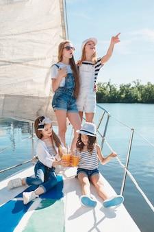 I bambini a bordo dello yacht del mare bevono succo d'arancia