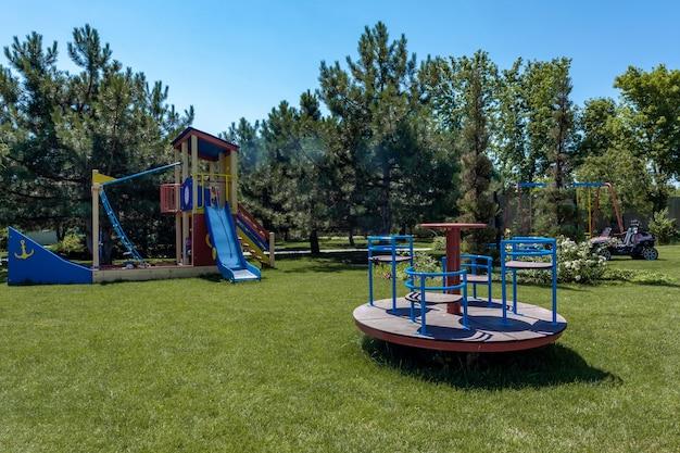여름에는 녹색 잔디에 미끄럼틀과 회전목마가 있는 어린이 보트 모양의 놀이 단지