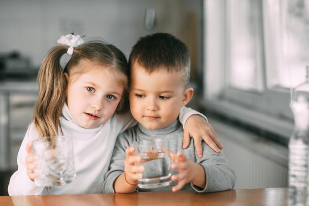台所で子供たちの男の子と女の子がグラスから水を飲み、抱きしめ、とても甘い笑顔