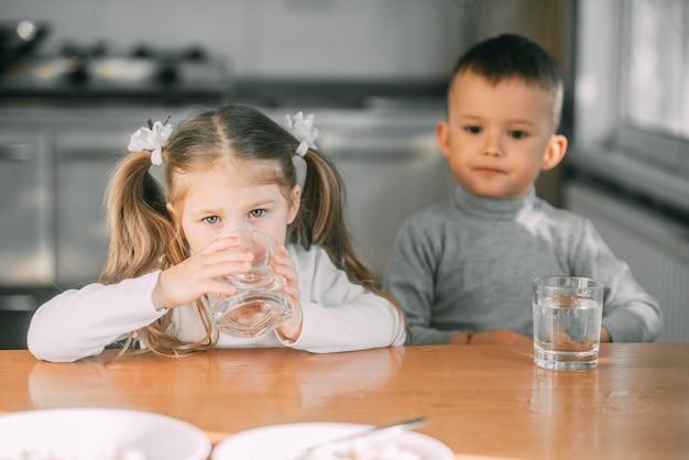 とても甘いグラスから水を飲む台所の子供たちの男の子と女の子