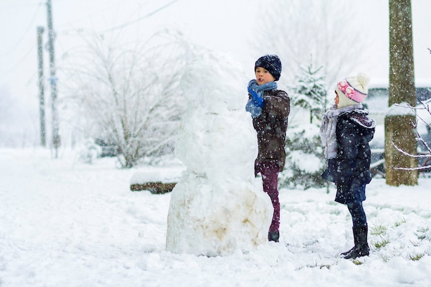 눈 덮인 겨울에 야외에서 어린이 소년과 소녀가 큰 눈사람을 만들고 있다