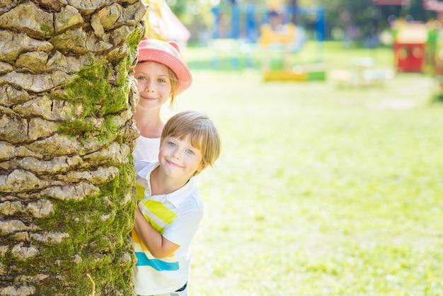 Дети мальчик и девочка, играющие на детской площадке, выглядывают из-за ствола пальмы. игра в прятки