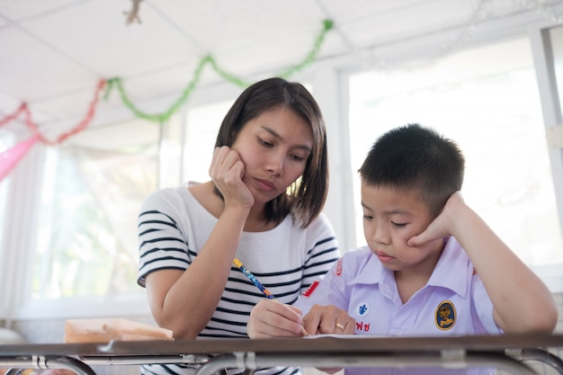 Children boy doing homework with mother