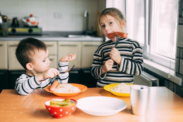 キッチンソーセージとパスタで食べる子供たちの男の子