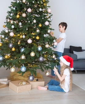 Children - a boy and a girl are playing near the christmas tree. living room interior with christmas tree and decorations. new year. gift giving.
