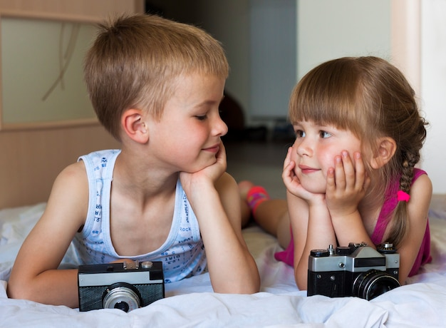 Children boy and girl brother and sister playing with cameras looking at each other.