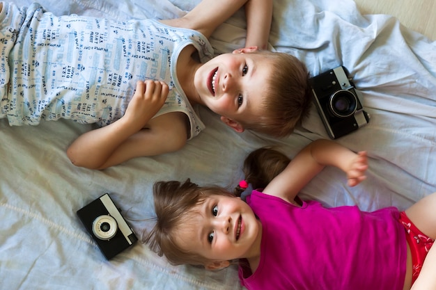 Children boy and girl brother and sister playing with cameras.