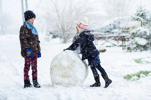 Children boy and girl outdoors in snowy winter are making a big snowman