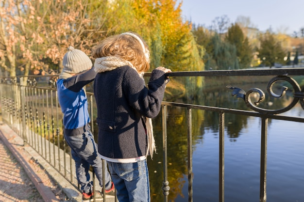 Children boy and girl standing backs on bridge, looking at ducks