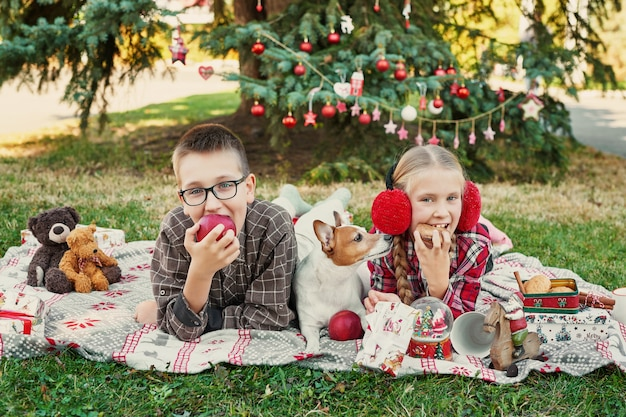Children boy and girl with a dog jack russell terrier near a christmas tree with gifts
