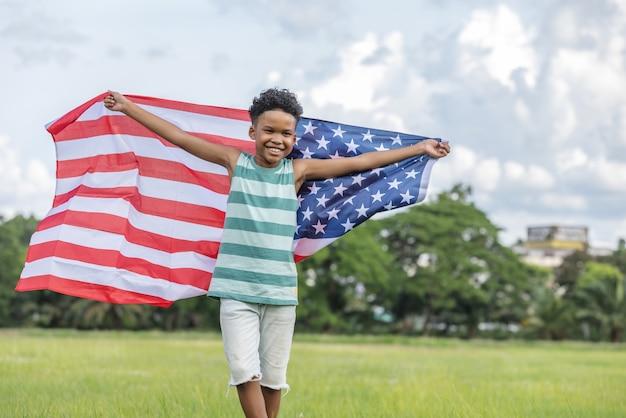 Children boy holding waving american usa flag running