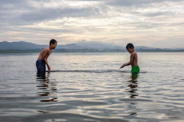 Детский мальчик, играющий в воде, счастлив и весел.
