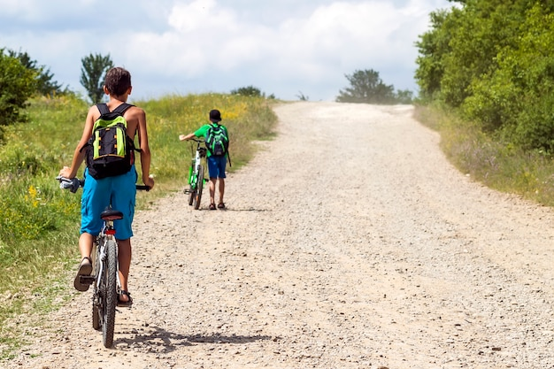 Children boys riding bicycles on a gravel road on a sunny day