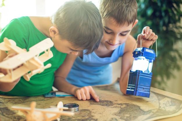 Дети мальчики с самолетом в руке, исследуйте карту ниже, чтобы путешествовать в новые приключения.