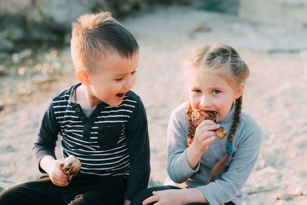 Дети, брат и сестра весело едят курицу шин на пляже у моря и скал, очень аппетитно