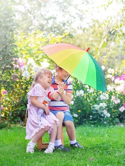 Children brother and sister are standing with an umbrella in the rain