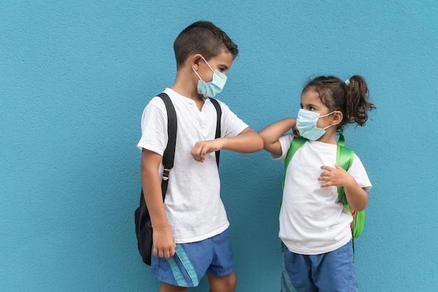 아이들은 학교 밖에서 포옹으로 인사하는 대신 팔꿈치를 부딪친다 - 소년 팔에 대한 주요 초점