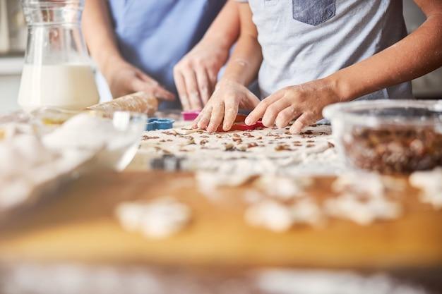 테이블에서 조심스럽게 반죽을 쿠키로 만드는 아이들