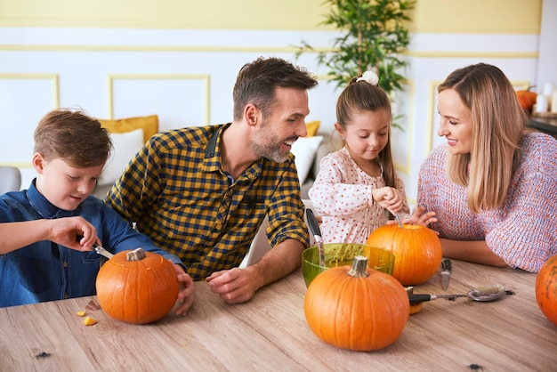 Children carving pumpkins with parents
