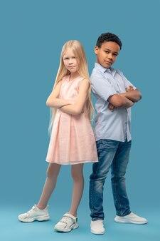 子供達。ドレスを着た白人の長髪の少女とシャツとジーンズの浅黒い肌の少年が手を組んで同じ位置に立っています