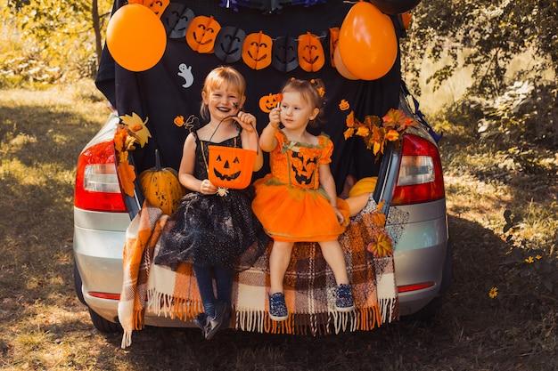 車のトランクでハロウィーンを祝う子供たち
