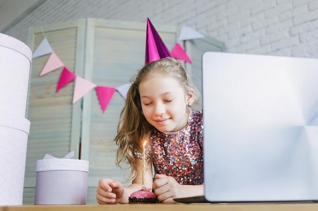 Дети празднуют ее день рождения через виртуальную вечеринку по видеосвязи с друзьями. гасит свечу.
