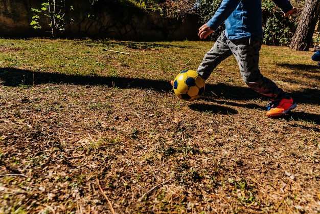 Children chasing an old soccer ball in a friendly match in summer.