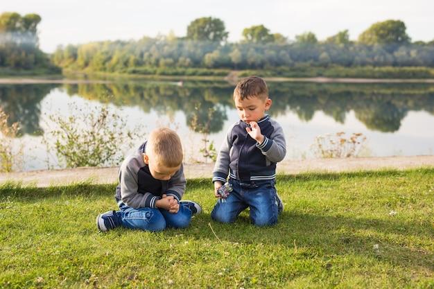 子供、子供時代、人々の概念-川の近くのビーチで遊ぶ子供たちの男の子。
