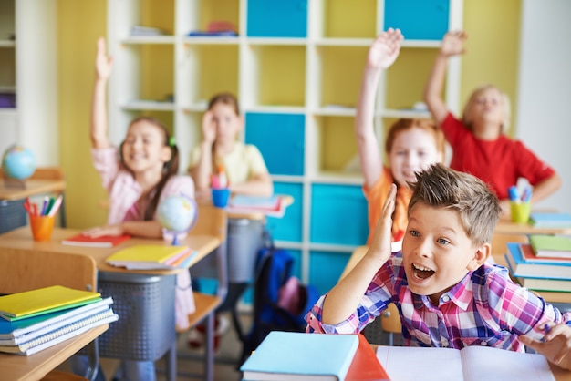 Children in the classroom with theirs hands up Free Photo