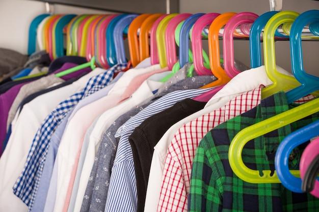 Детская одежда на вешалках в шкафу для одежды с одеждой для мальчиков на вешалках, концепция покупок
