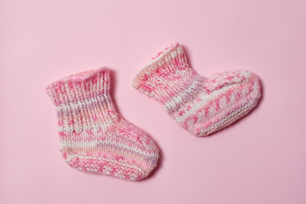Children clothes  on a white . pink knitted booties. isolate