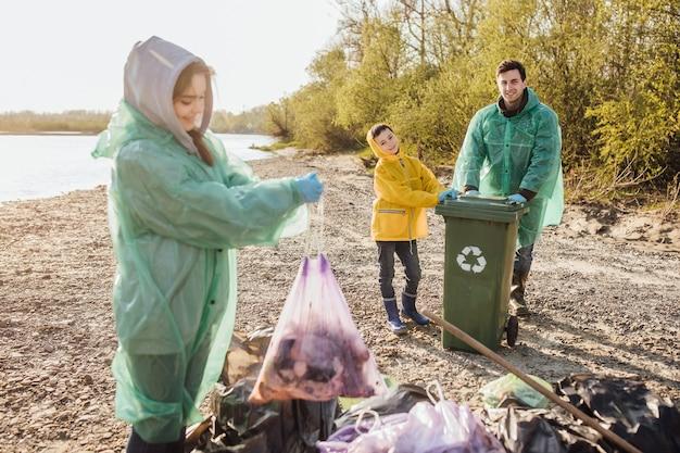 I bambini raccolgono il sacco della spazzatura nel bosco