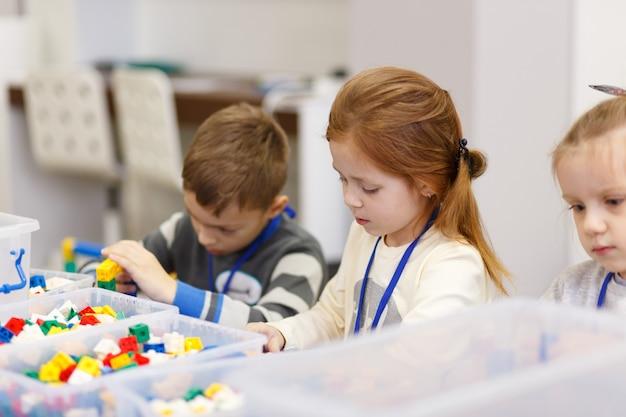 子供たちはデジタル技術の学校でコンストラクターのプラスチック部品からさまざまなオブジェクトを収集します
