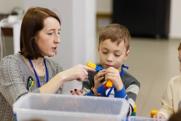 Дети собирают различные предметы из пластмассовых деталей конструктора в школе цифровых технологий