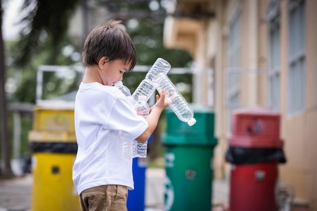 Дети собирают пластиковые бутылки с водой и выбрасывают пустую пластиковую бутылку в мусор