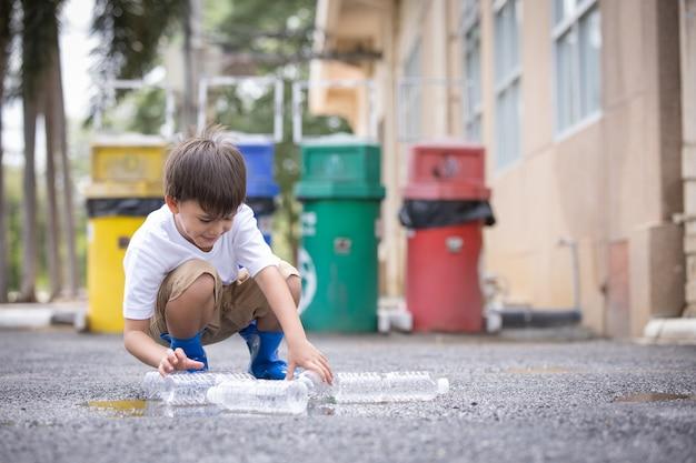Дети собирают пустые пластиковые бутылки из-под воды, чтобы выбросить их в мусорную корзину