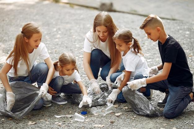 아이들은 공원에서 쓰레기 봉투에 쓰레기를 수집