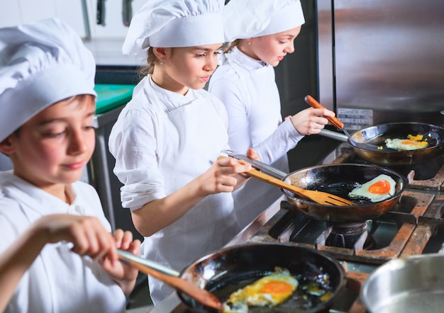 レストランのキッチンでランチを調理する子供たち。