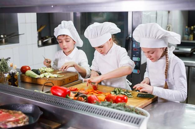 Children cooking lunch in a restaurant kitchen.