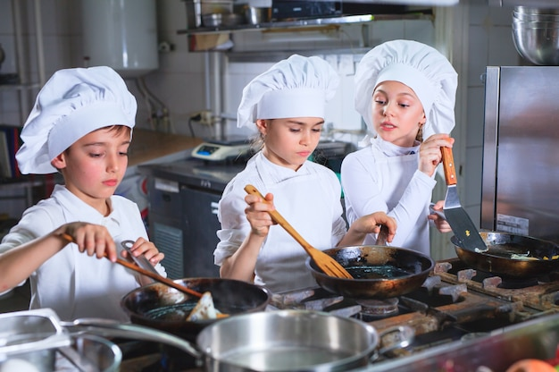 Children cooking lunch in a restaurant kitchen.