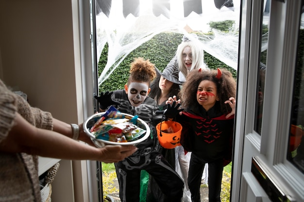 Children in costumes trick or treating on halloween