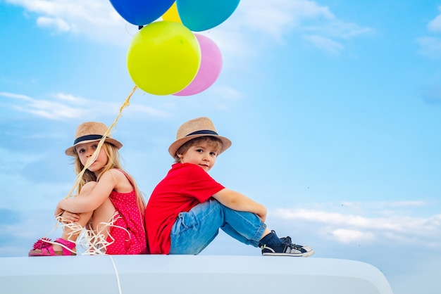 Children on countryside on sky background isolated little boy with little girl  kids couple in love ...