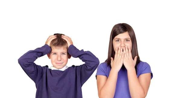 Children covering the ears and shocked by a loud sound isolated on a white