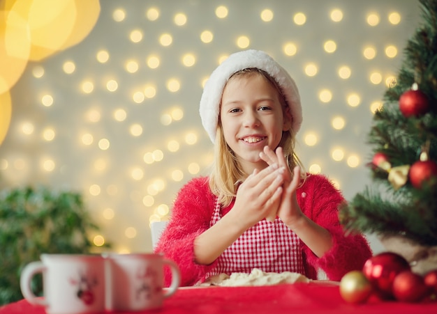Дети вырезают печенье из сырого теста формочкой для печенья