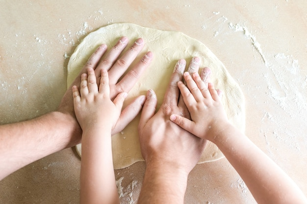 Children and dad hands on dough
