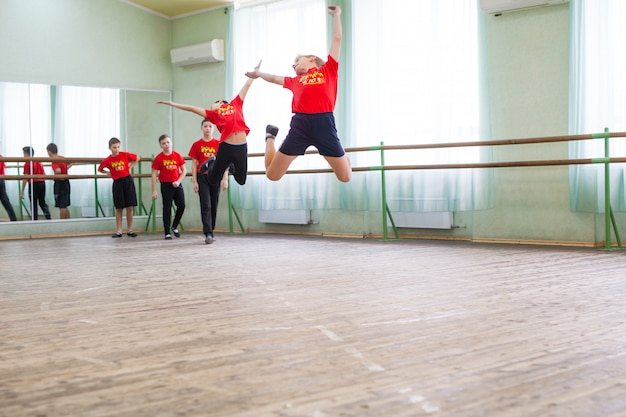 Children dance with a trainer in a large training room.