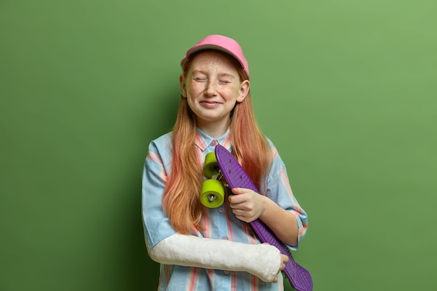 Children, dangerous hobby and injuries concept. pleased redhead girl closes eyes and feels happy, holds skateboard under arm, got trauma during skateboarding, has active summer rest, isolated on green