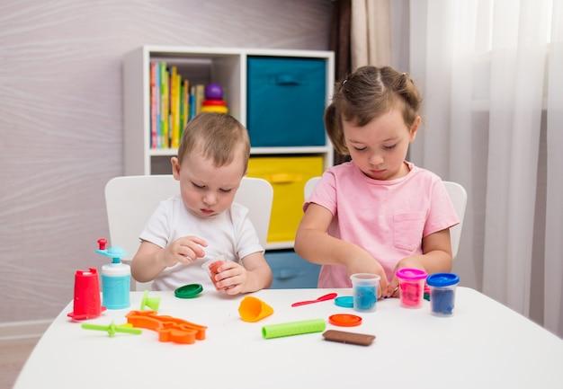 子供たちは部屋のテーブルで粘土で遊ぶ細かい運動能力を発達させる